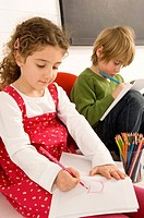 Two children drawing on a notepad
