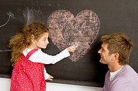 Side profile of a girl drawing on the blackboard with her father watching her