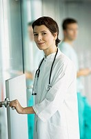 Portrait of a female doctor holding a door handle and smiling (thumbnail)