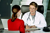 Male doctor discussing with a female patient in his office