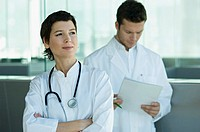 Female doctor standing with a male doctor holding medical records behind her