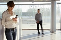 Businesswoman using a mobile phone with a businessman walking in the background
