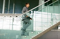 Businessman carrying a laptop and moving up a staircase