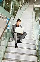 Low angle view of a businessman sitting on a staircase and using a laptop