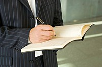 Mid section view of a businessman writing in a diary