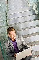 High angle view of a businessman sitting on a staircase and using a laptop