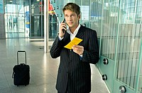 Businessman holding an airplane ticket and talking on a mobile phone