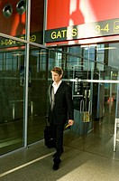 Businessman walking with his luggage at an airport (thumbnail)