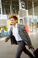 Side profile of a businessman rushing with his luggage at an airport