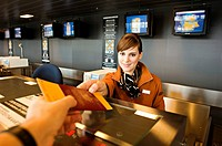 Female airline check_in attendant giving a passport and boarding pass to a passenger