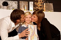Young woman and a mid adult man kissing their daughter