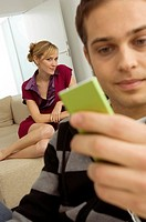 Close_up of a young man holding an MP3 player with a young woman sitting behind him