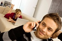 Young man using a mobile phone with a young woman using a laptop in the background