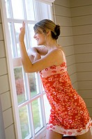 Young woman looking through a window and smiling