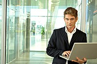 Businessman standing and using a laptop at an airport