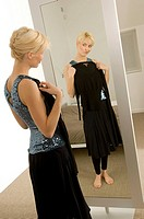 Young woman trying on a dress in front of a mirror (thumbnail)