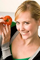 Portrait of a young woman showing a tomato (thumbnail)