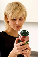 Close_up of a young woman reading a label on a jar