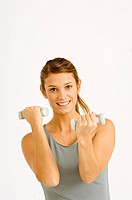 Portrait of a young woman exercising with dumbbells (thumbnail)
