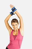 Portrait of a young woman stretching with her arms raised (thumbnail)