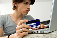 Close_up of a teenage boy using a laptop and holding a credit card