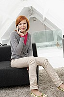 Young woman sitting on a couch and using a mobile phone (thumbnail)