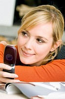 Close_up of a young woman using a mobile phone and smiling