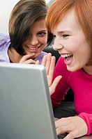 Two young women using a laptop