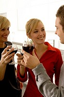Two young women and a young man toasting with wine glasses