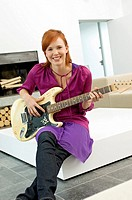 Portrait of a young woman sitting with a guitar on a coffee table and smiling