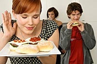 Young woman holding burgers in a tray with her friends in background