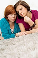 Close_up of two young women lying on a carpet and looking serious