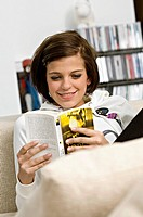 Young woman sitting on a couch and reading a book