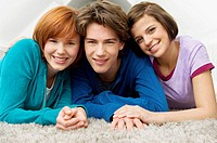 Portrait of a teenage boy smiling with two young women