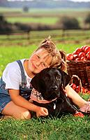 girl and Labrador Retriever on meadow