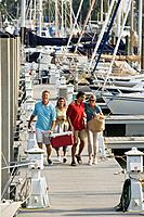Friends walking along yachting pier