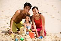 Family making a sand castle at beach