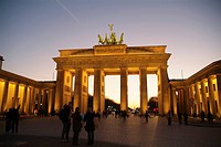 Tourists near memorial gate lit up at dusk, Brandenburg Gate, Berlin, Germany