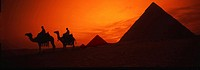 Silhouette of two people sitting on camel in desert, Cairo, Egypt
