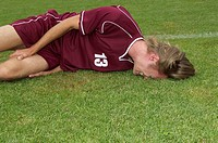 Injured kicker lying on soccer field