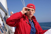 Young man looking through a telescope on a sailing boat
