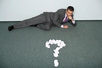 Reflective businessman lying on floor, question mark of crushed papers in front