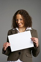 Smiling businesswoman holding blank sign at camera