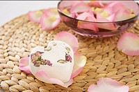 A heart_shaped piece of soap on rose petals