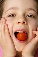 Boy eating a tomato