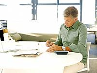 Businessman filling out paperwork in office