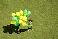 Young girl holding bunch of balloons