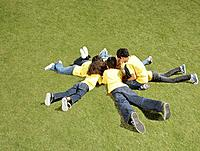 Group of children laying in grass in circle formation