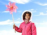 Young girl in winter coat holding spinning pinwheel