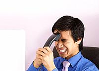 Businessman grimacing while holding telephone handset